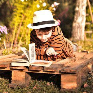Garoto lendo um livro ao ar livre